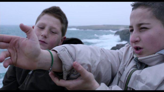 Dwójka chłopców nad morzem udających że ich ręce to pistolety