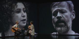 Kobieta i mężczyzna na scenie z instrumentami, w tle ich czarno-białe twarze