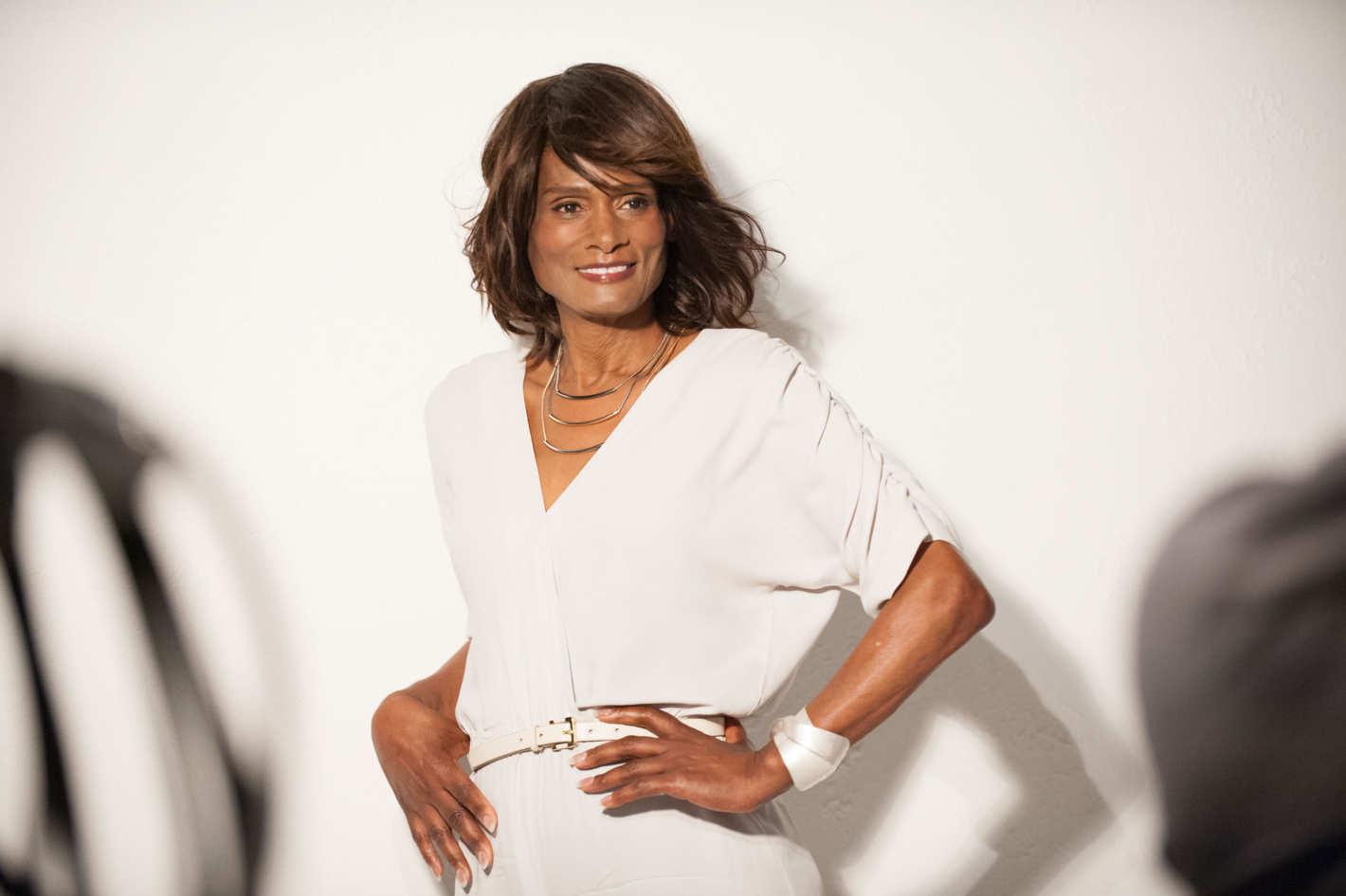 Czarnoskórka kobieta w białej sukience na tle ściany