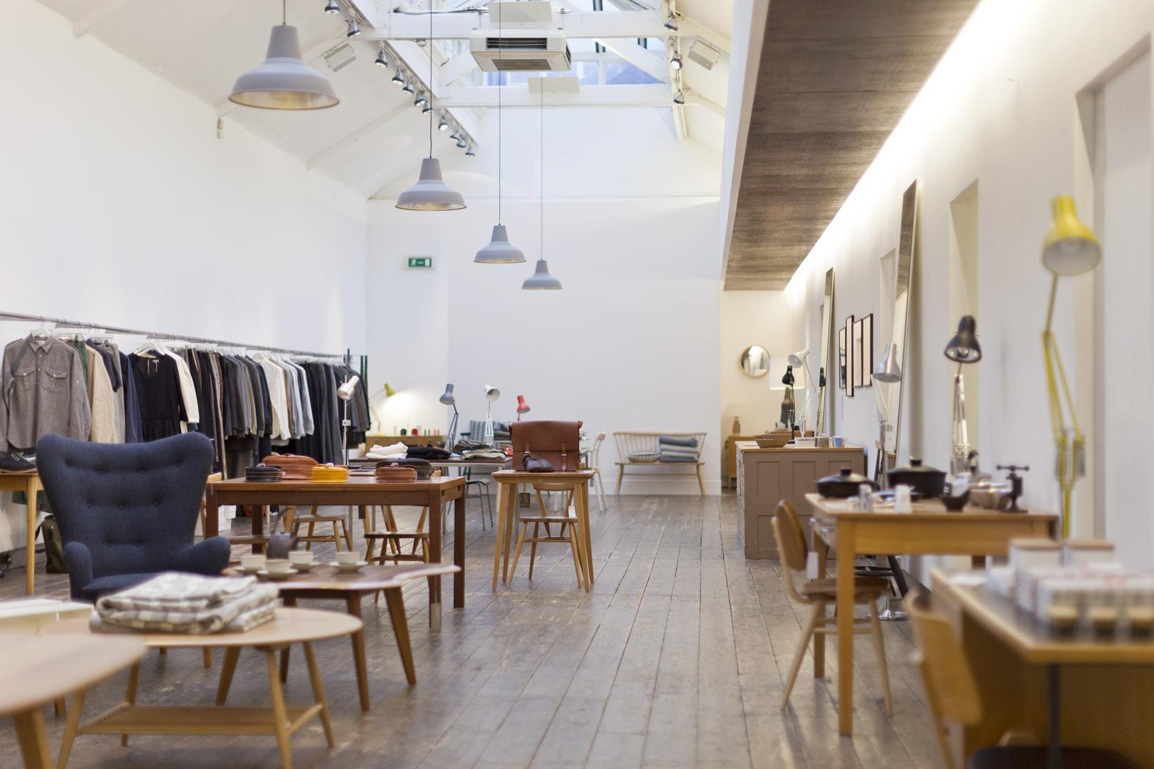 Drewniane stoły, żyrandole i białe ściany we wnętrzu sklepu