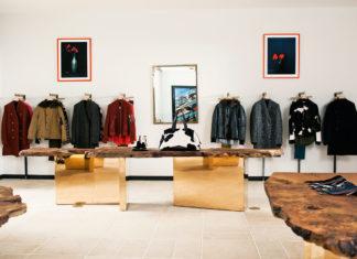 Kolorowe kurtki na wieszakach, białe ściany we wnętrzu sklepu