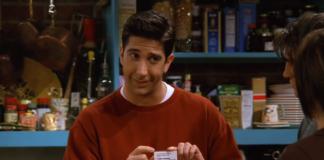 Mężczyzna w czerwonym swetrze trzyma małą karteczkę