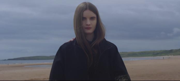 Dziewczyna z długimi brązowymi włosami i w czarnym płaszczu