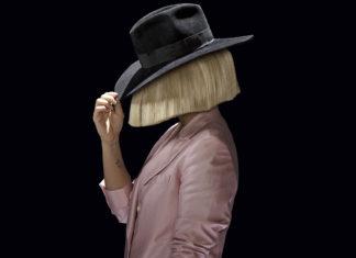 Kobieta w peruce blond i czarnym kapeluszu ubrana w różową marynarkę