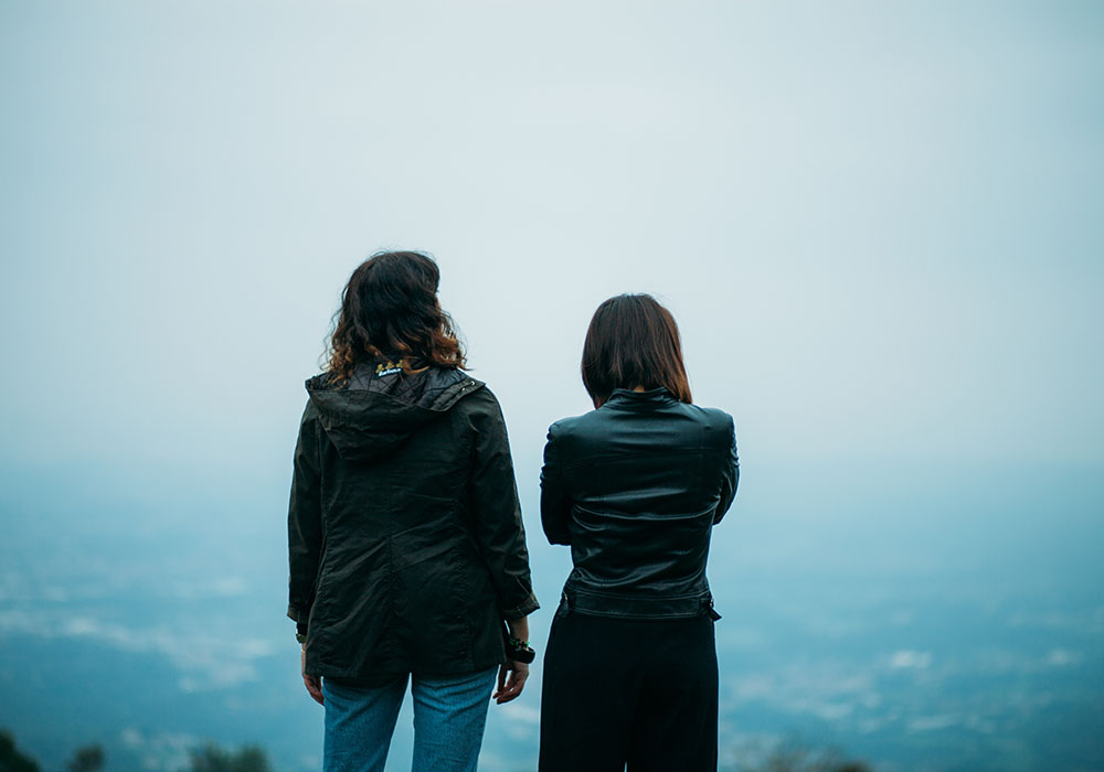 Dwie dziewczyny odwrócone tyłem, w ciemnych kurtkach