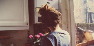 Dziewczyna w niebieskiej bluzce z kokiem stoi tyłem, obok bukiet kwiatów