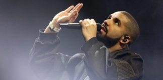 Mężczyzna ubrany na czarno śpiewa do mikrofonu