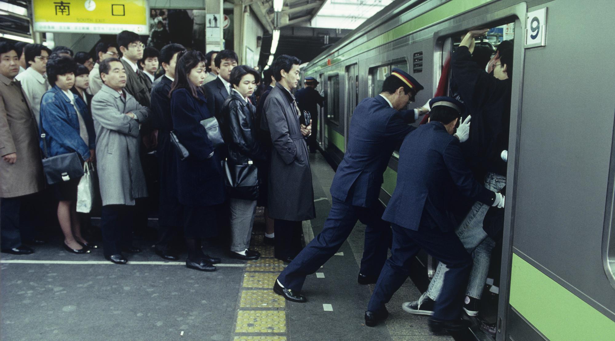 Tłum ludzi w japońskim metrze, konduktorzy upychają pasażerów
