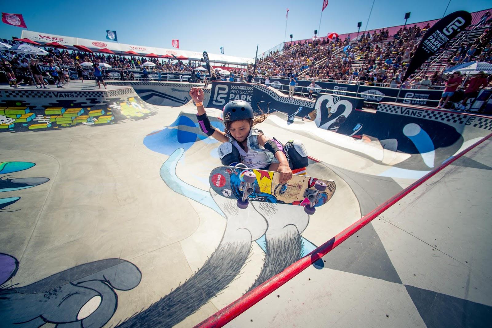 Dziewczynka w kasku na deskorolce, jeżdżąca na zawodach na rampie
