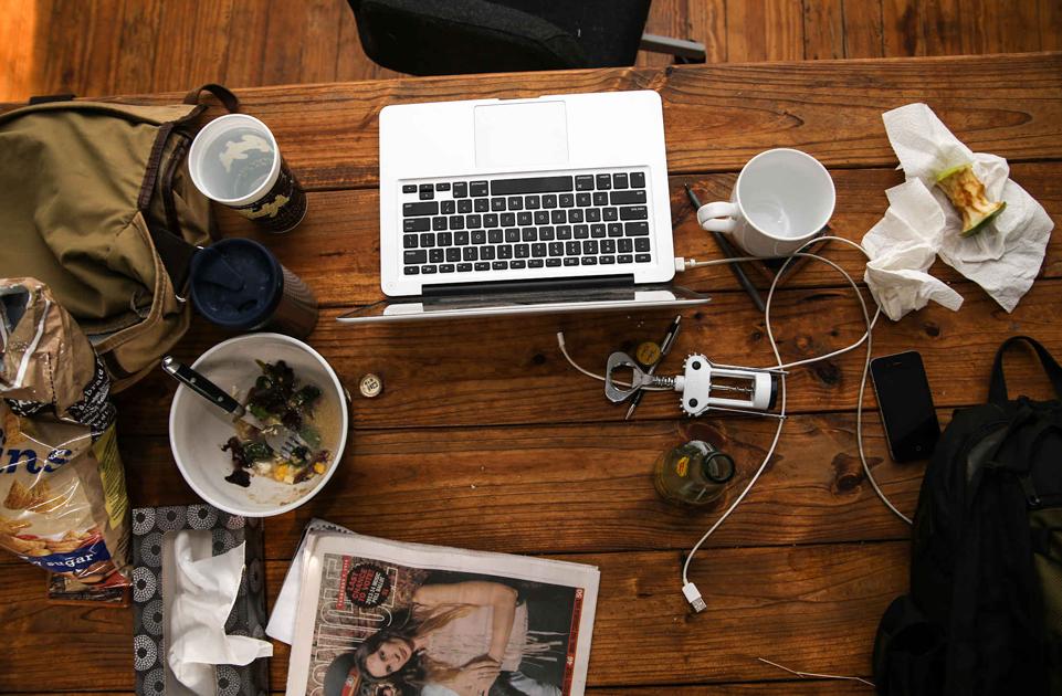Nieuporządkowane biurko na którym jest miska po jedzeniu, laptop, ogryzek i kubek