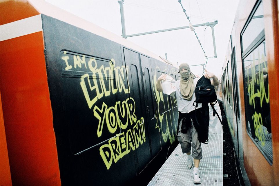 Chłopak z zasłonietą twarz na tle graffiti