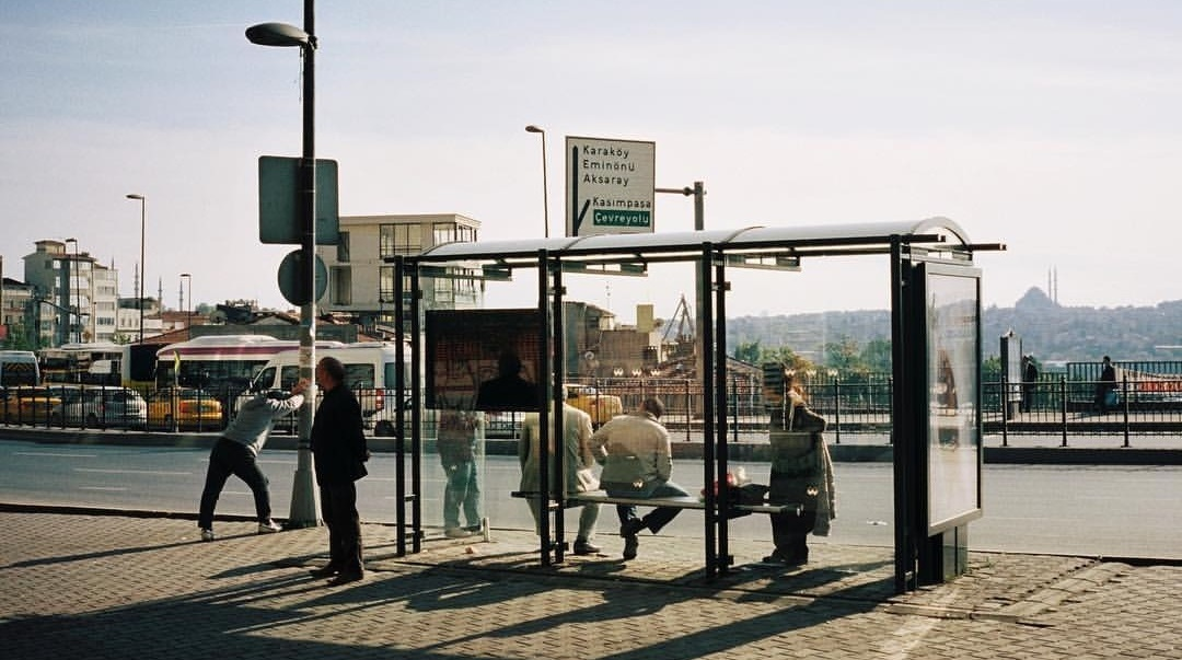 Grupa ludzi na przystanku autobusowym czeka na autobus