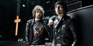 Dwóch mężczyzn w czarnych skórzanych kurtkach stoi na scenie