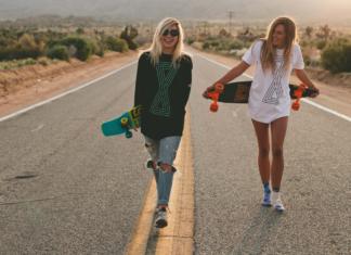 Dwie młode dziewczyny trzymające longboardy, stoją na środku pustej ulicy z deskorolkami