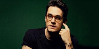 Mężczyzna ubrany na czarno z tatuażem na ręku i w okularach