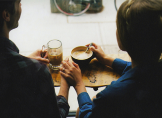 Dwie osoby siedzą tyłem z filiżankami kawy