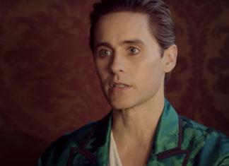Mężczyzna w zielonym płaszczu na czerwonym tle