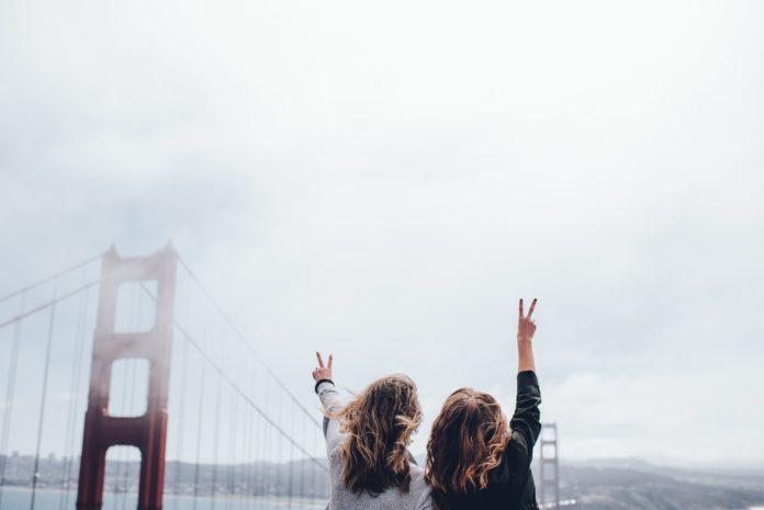 Dwie dziewczyny odwrócone tyłem pokazują znak Victorii na moście