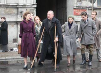 Mężczyzna w czarnym płaszczu o kulach, obok trzy kobiety w płaszczach i mężczyzna