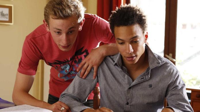 Chłopak w czerwonej koszulce i chłopak w szarej koszuli siedzą przy biurku