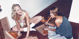 Blondynka i brunetka jedzą pizzę na podłodze
