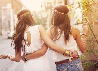 Dwie dziewczyny z długimi włosami w białych bluzkach idą tyłem