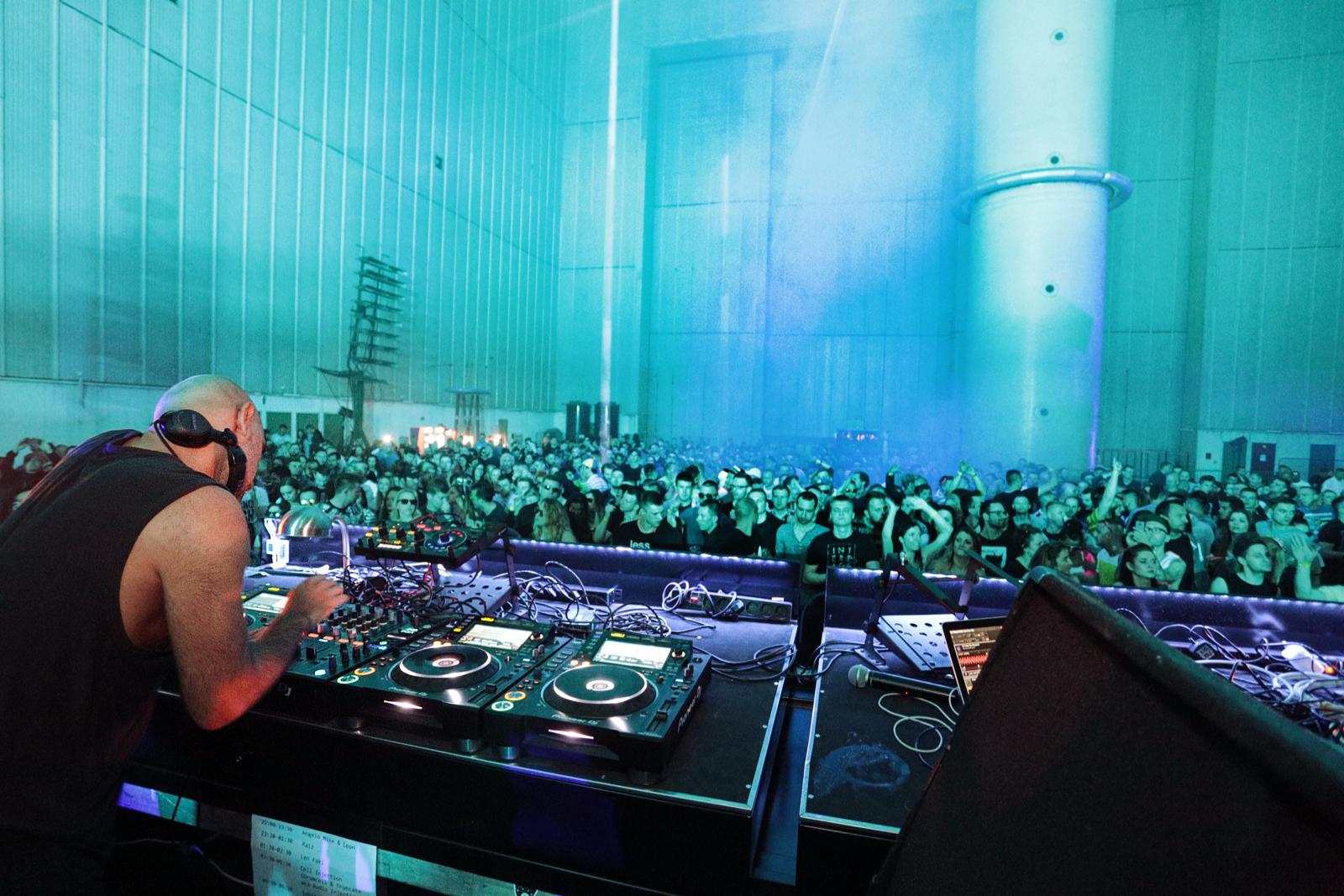 DJ i tłum imprezujących ludzi na błękitnym tle wielkiej hali
