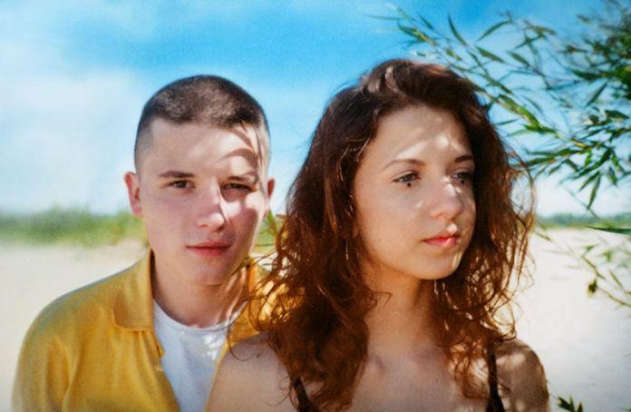 Młody, łysy chłopak stojący obok dziewczyny z kręconymi włosami
