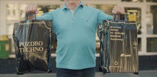 Starszy mężczyzna trzymający w rękach siatki reklamowe promujące festiwal Up To Date