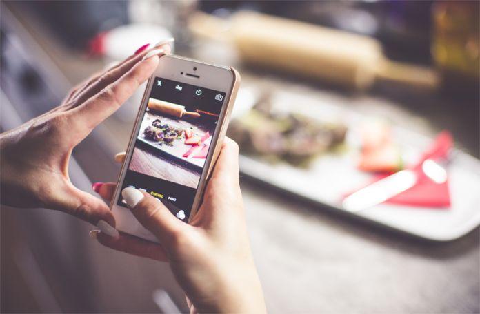 Dłonie trzymające telefonem, który robi zdjjęcia jedzeniu