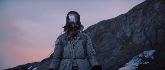Postać z cyfrową twarzą stojąca w kurtce wśród gór