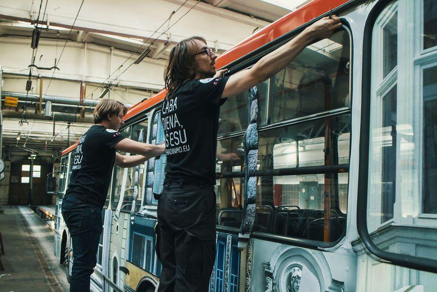Dwóch mężczyzn ubranych na czarno maluje trolejbus