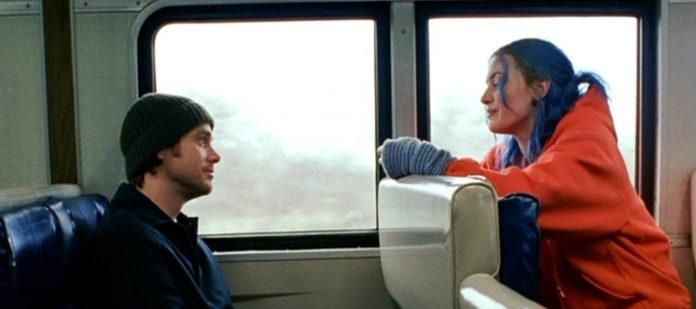 Dziewczyna z niebieskimi włosami w czerwonej kurtce i mężczyzna w czapce rozmawiają w pociągu
