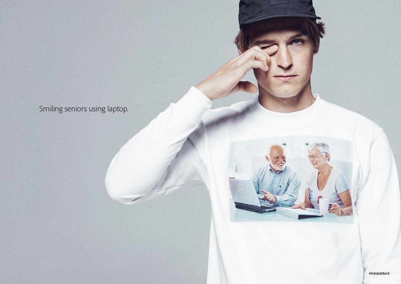 Mężczyzna w białej koszulce z nadrukiem, przedstawiającym dwójkę emerytów przed komputerem