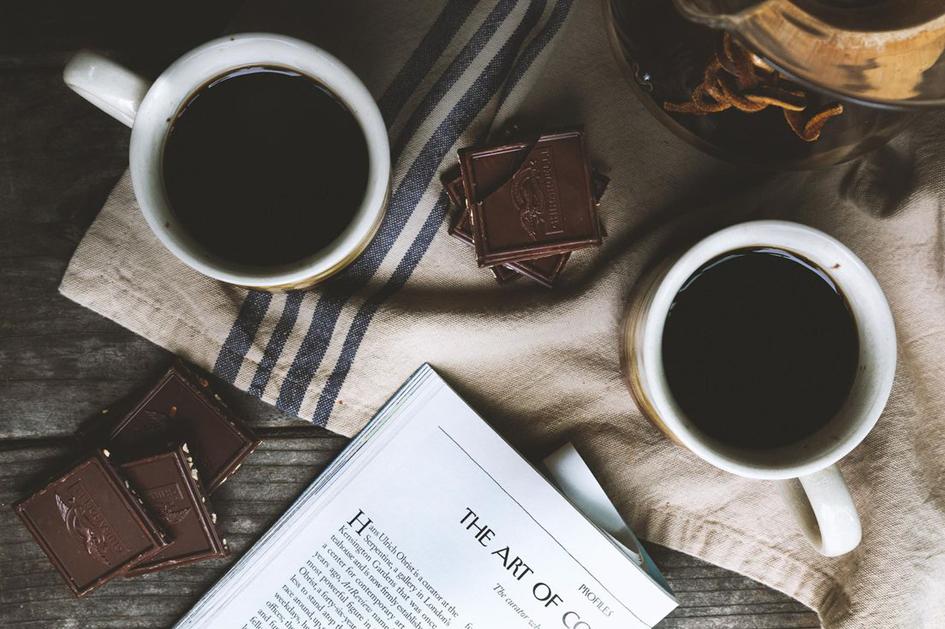 Dwie filiżanki kawy, książka, obrus i czekolada
