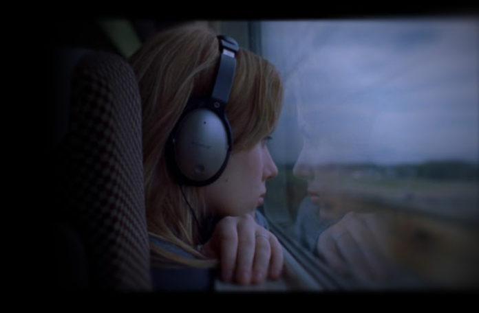 Dziewczyna ze słuchawkami na uszach patrzy przez okno w pociągu