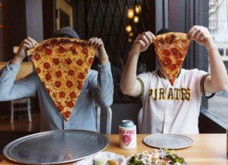 Dwie osoby siedzą przy stoliku i zakrywają sobie twarz wielkimi kawałkami pizzy