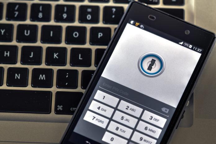 telefon leży na klawiaturze komputera i ma włączoną aplikacją 1password