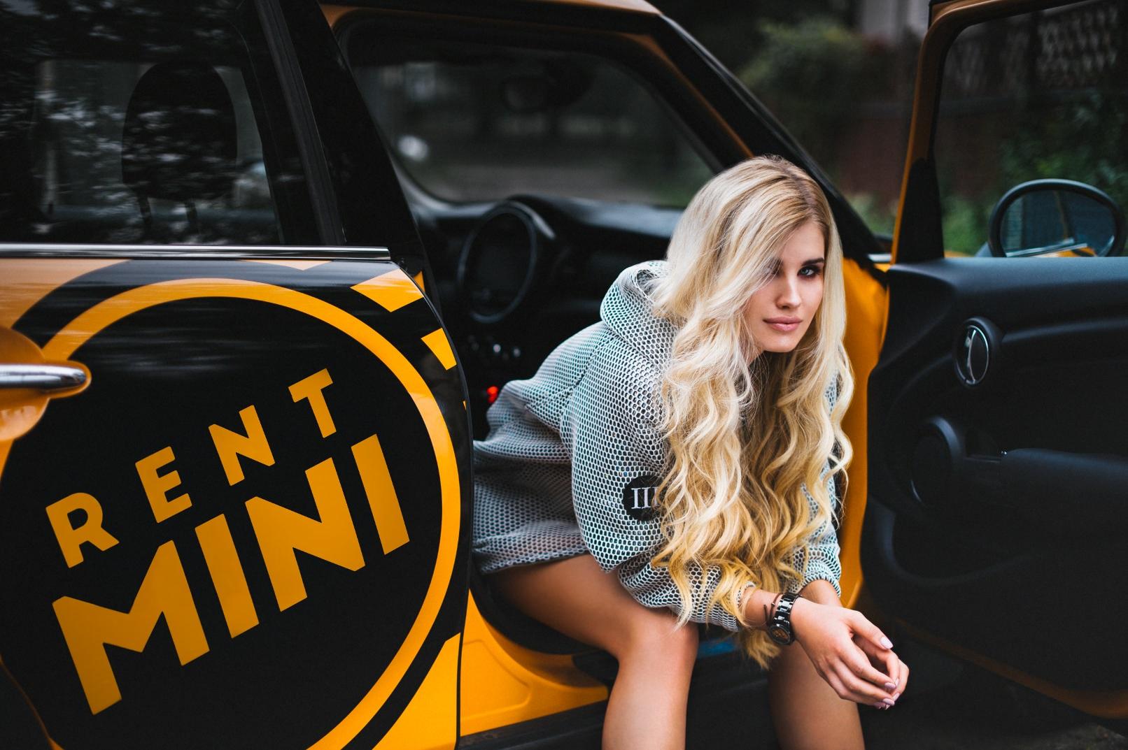 Blondynka w szarej bluzie siedzi w żółtym samochodzie