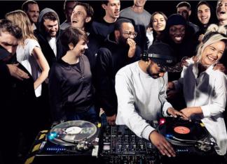 Grupa ludzi ubranych na czarno na imprezie, chłopak w białej bluzie za konsoletą