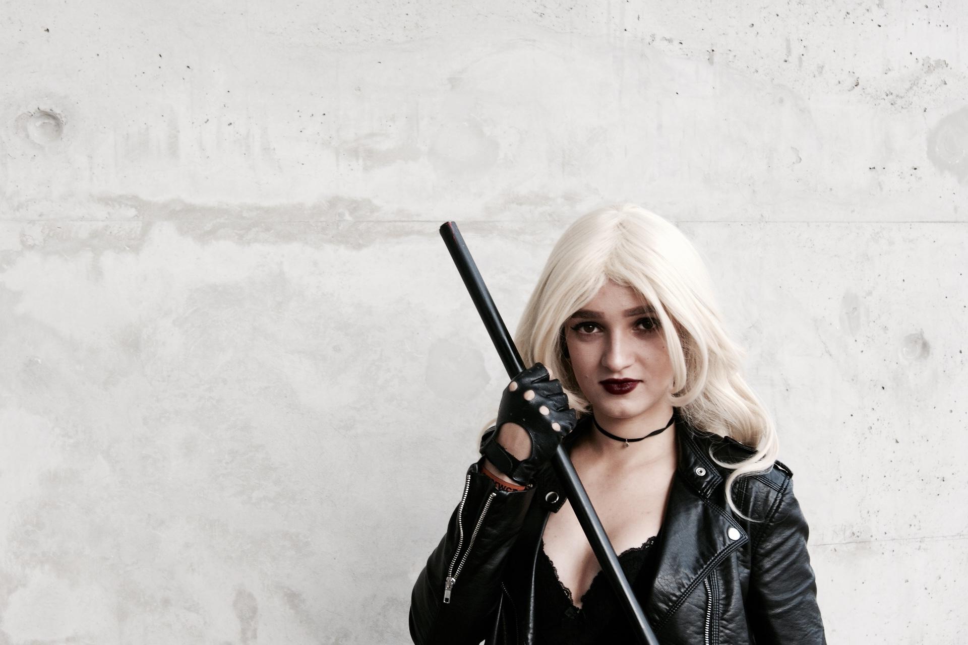 Dziewczyna w blond peruce ubrana na czarno z łukiem