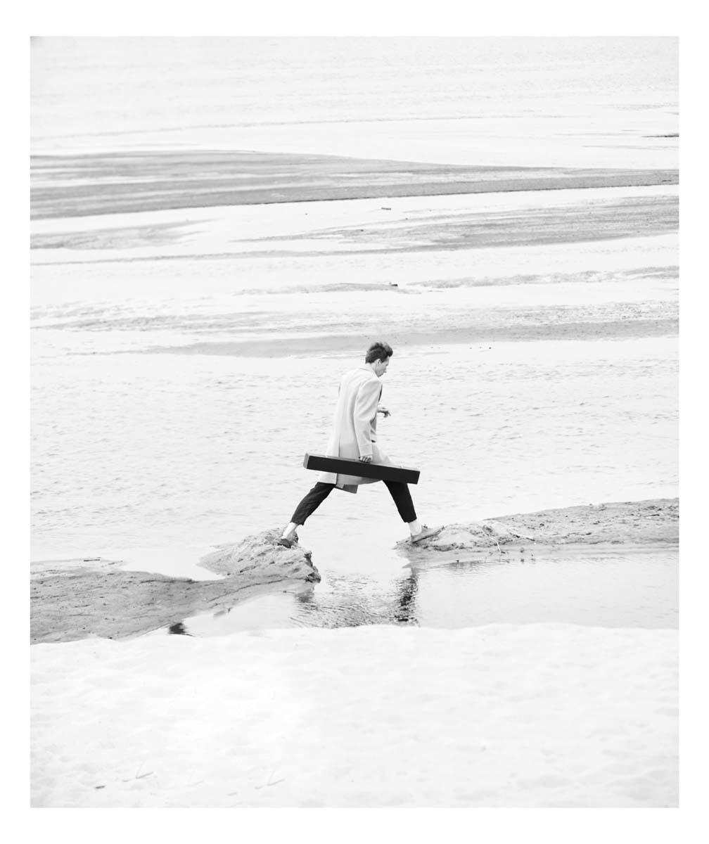 Mężczyzna w białym płaszczu i futerałem biegnie po wodzie