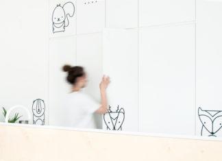 Kobieta w kucyku i białym t-shircie na tle białej ściany