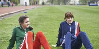 Dwie dziewczyny w sportowych ubraniach siedzą na boisku szkolnym