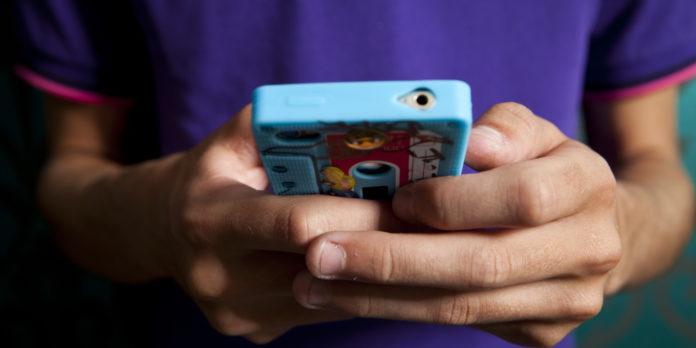 Ręce chłopaka trzymającego telefon w kolorowej obudowie