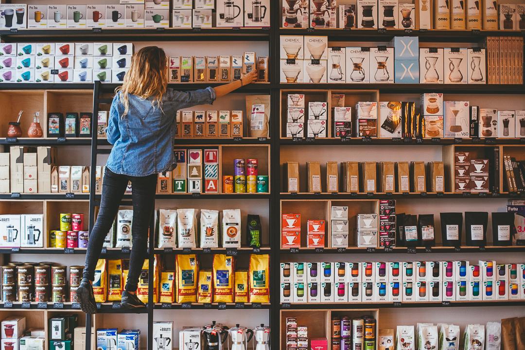 Dziewczyna w dżinsowej kurtce stoi na stołku i sięga na półki z kawą