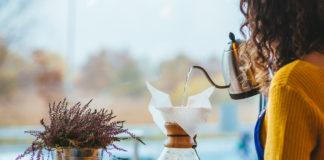 Kobieta w żółtym sweterku w kawiarni piję kawę przy stoliku, obok stoi wrzos