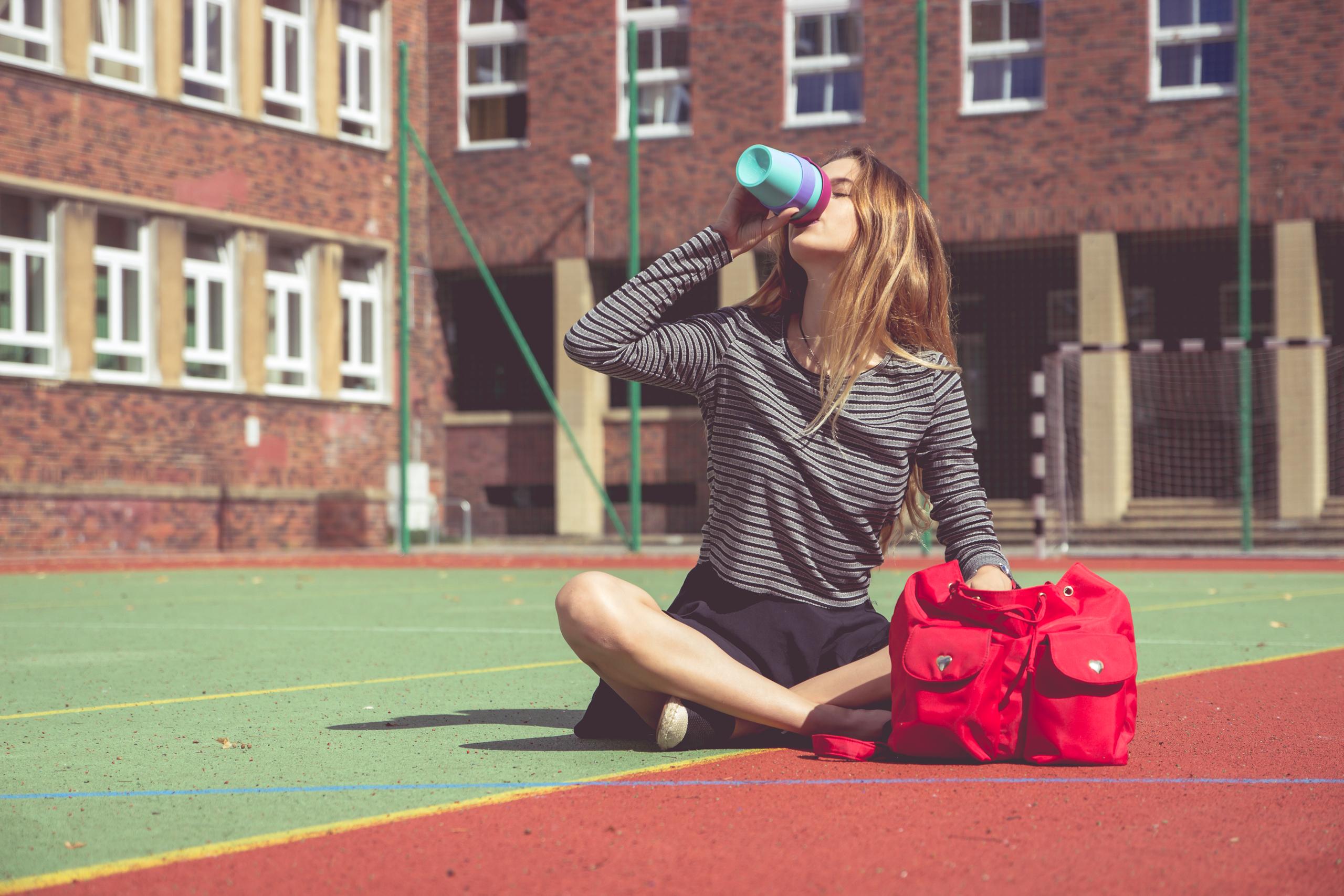 Dziewczyna z czerwonym plecakiem siedzi na boisku szkolnym i piję kawę z niebieskiego kubka