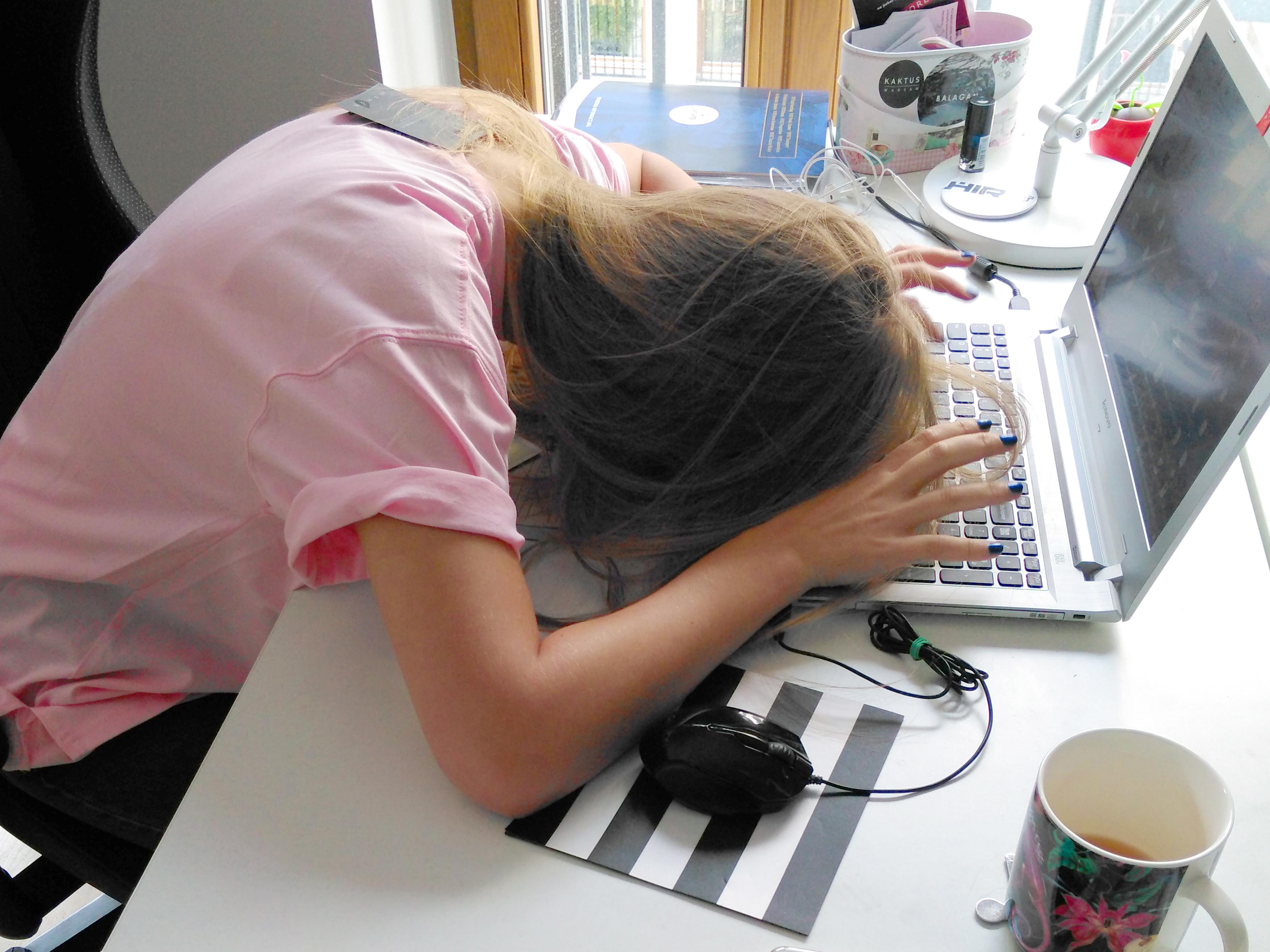 Kobieta w różowym t-shircie leży na biurku z twarzą zasłoniętą włosami