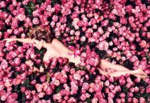 Naga kobieta w płatkach różowych róż
